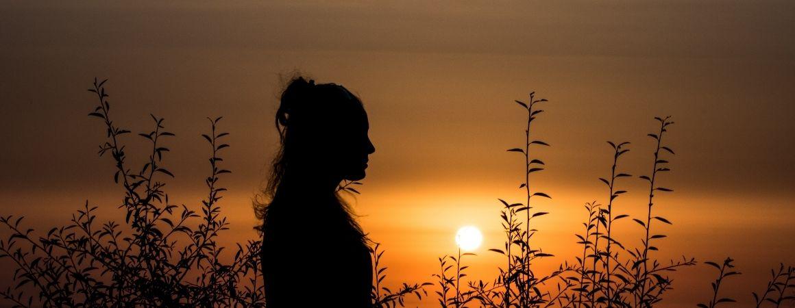 Abnehmblockaden: Frau steht im Dunklen auf der Wiese